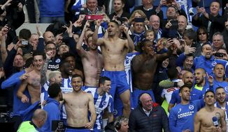Brighton and Hove Albion players and fans celebrate promotion following the EFL Championship match between Brighton and Wigan Athletics, at the AMEX Stadium, in Brighton, England, Monday April 17, 2017. Brighton will return to the topflight of English soccer for the first time in 34 years after securing promotion to the Premier League on Monday. (Gareth Fuller/PA via AP)