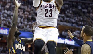 Cleveland Cavaliers' LeBron James catches a pass against Indiana Pacers' Lance Stephenson, left, and Monta Ellis, right, in the first half in Game 2 of a first-round NBA basketball playoff series, Monday, April 17, 2017, in Cleveland. (AP Photo/Tony Dejak)