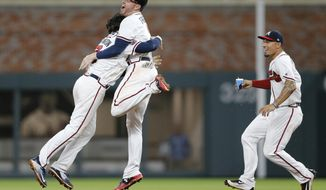 Atlanta Braves' Dansby Swanson, left, celebrates with Freddie Freeman as Jace Peterson rushes in after hitting a game-winning base hit in the ninth inning of a baseball game against the San Diego Padres, Monday, April 17, 2017, in Atlanta. Atlanta won 5-4. (AP Photo/John Bazemore)