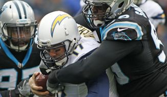 FILE - In this Dec. 11, 2016, file photo, San Diego Chargers' Philip Rivers (17) is sacked by Carolina Panthers' Kawann Short (99) in the first half of an NFL football game in Charlotte, N.C. The Carolina Panthers have signed Kawann Short to a five-year contract extension, keeping the defensive tackle with the team through the 2021 season. A person familiar with the deal says the extension is worth $80 million. The person spoke to The Associated Press on condition of anonymity Monday, April 17, 2017, because the team doesn't release financial terms of contracts.(AP Photo/Bob Leverone, File)