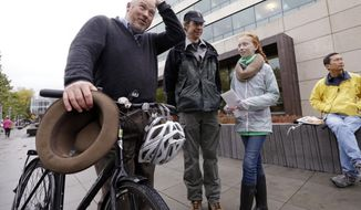 FILE - In this 28, 2015 file photo, teenage environmental activists Wren Wagenbach, 14, second right, stands with her father, Mike Wagenbach, as they talk with former Seattle mayor Mike McGinn, left, before a rally in Seattle, Wash. McGinn announced on Monday, April 17, 2017, that he will challenge incumbent Seattle Mayor Ed Murray, who defeated McGinn in 2013. (AP Photo/Elaine Thompson, file)