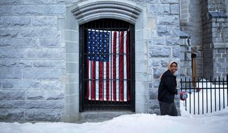 ADVANCE FOR USE WEDNESDAY, APRIL 19, 2017 AND THEREAFTER-A U.S. flag hangs at the Franco American Heritage Center as a woman enters to attend the local high school's pre-prom fashion show in Lewiston, Maine, Thursday, March 16, 2017. Maine is the whitest state in America, 95 percent white, and its citizens were abruptly confronted with hundreds of black Muslims, traumatized by war and barely able to speak English. (AP Photo/David Goldman)