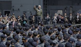 U.S. Vice President Mike Pence, center top, waves before he speaks to U.S. servicemen and Japanese Self-Defense Forces personnel on the flight deck of U.S. navy nuclear-powered aircraft carrier USS Ronald Reagan at the U.S. Navy's Yokosuka base in Yokosuka, south of Tokyo, Wednesday, April 19, 2017. (AP Photo/Eugene Hoshiko)