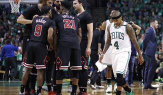 Boston Celtics guard Isaiah Thomas (4) walks past the Chicago Bulls as they huddle during the second quarter of a first-round NBA playoff basketball game in Boston, Tuesday, April 18, 2017. (AP Photo/Charles Krupa)