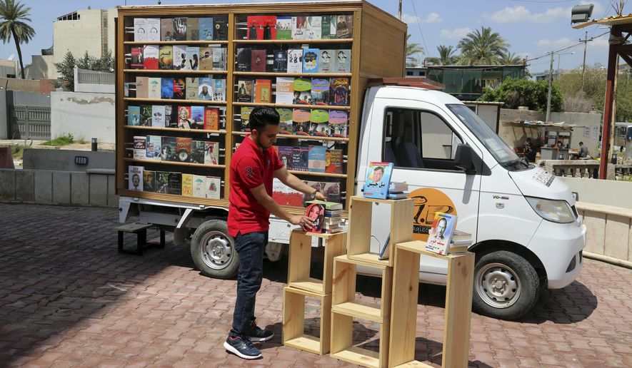 In this Sunday, April 16, 2017 photo, Ali al-Moussawi, the owner of a mobile library truck, arranges his books on a street in Baghdad, Iraq. The mobile bookstore is the latest in a series of efforts by the 25-year-old to share his passion for reading and revive a love for books in Baghdad, which was once the literary capital of the Muslim world but is now better known for bombs than poems.(AP Photo/Karim Kadim)