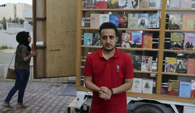 In this Sunday, April 16, 2017 photo, Ali al-Moussawi, stands in front of his book truck on a street in Baghdad, Iraq. The mobile bookstore is the latest in a series of efforts by the 25-year-old to share his passion for reading and revive a love for books in Baghdad, which was once the literary capital of the Muslim world but is now better known for bombs than poems.(AP Photo/Karim Kadim)