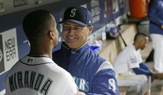 Seattle Mariners starting pitcher Ariel Miranda is greeted by manager Scott Servais after Miranda pitched seven scoreless innings against the Miami Marlins in a baseball game, Monday, April 17, 2017, in Seattle. (AP Photo/Ted S. Warren)