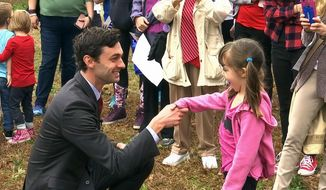 "Democratic congressional candidate Jon Ossoff is seen with supporters outside of the East Roswell Branch Library in Roswell, Ga., on the first day of early voting, in this Monday, March 27, 2017, file photo. President Donald Trump is attacking Ossoff, the leading Democratic candidate for a special election in a typically conservative Georgia congressional district, with Republicans bidding to avoid a major upset. On Twitter, Trump said Monday April 17, 2017, that ""The super Liberal Democrat in the Georgia Congressional race tomorrow wants to protect criminals, allow illegal immigration and raise taxes!"" (AP Photo/Alex Sanz)"