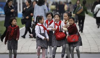 North Korean school girls react upon seeing their photograph being taken as they walk along Mirae Scientists Street on Wednesday, April 19, 2017, in Pyongyang, North Korea. Tensions have spiked in recent weeks over North Korea's advancing nuclear technology and missile arsenal. But in Pyongyang, where war would mean untold horrors, few people seem to care much at all. (AP Photo/Wong Maye-E)