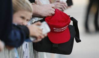 """A supporter holding a """"Make America Great Again,"""" hat waits to greet President Donald Trump when he arrives on Air Force One in West Palm Beach, Fla., Friday, Feb. 10, 2017. (AP Photo/Wilfredo Lee)"""