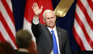 U.S. Vice President Mike Pence waves during a lecture for Japan-U.S. business leaders at a hotel in Tokyo, Wednesday, April 19, 2017. Pence made a pitch for President Donald Trump's economic policies, telling U.S. and Japanese business leaders that a tax overhaul and cut in regulations will help business on both sides of the Pacific. (AP Photo/Shizuo Kambayashi)
