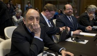 Roman Kolodkin, head of the legal department of the Russian Foreign Affairs ministry, left, waits for the judges to enter the World Court to deliver the order on provisional measures in The Hague, Netherlands, Wednesday, April 19, 2017, in the case brought by the Ukraine against Russia accusing Moscow of financing separatist rebels and racially discriminating against ethnic Tartars and Ukrainians in the annexed Crimea peninsula. (AP Photo/Peter Dejong)