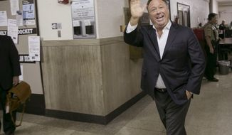 Alex Jones, a well-known Austin-based broadcaster and provocateur, arrives for a child custody trial at the Heman Marion Sweatt Travis County Courthouse in Austin, Texas, on Wednesday April 19, 2017.  Kelly Jones is seeking sole or joint custody of the couples' children, ages 14, 12 and 9. (Jay Janner/Austin American-Statesman via AP)