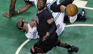 Chicago Bulls guard Dwyane Wade eyes the loose ball as Boston Celtics guards Isaiah Thomas and Marcus Smart, top, land on the floor during the fourth quarter of a first-round NBA playoff basketball game in Boston, Tuesday, April 18, 2017. The Bulls defeated the Celtics 111-97 and take a 2-0 lead in the series. (AP Photo/Charles Krupa)