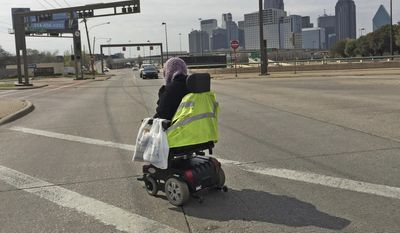 ADVANCE FOR PUBLICATION RELEASE MONDAY, APRIL 24, 2017, AT 12:01 A.M. CT AND THEREAFTER  In this March 15, 2017 photo, Mythia Joseph crosses the street in her motorized wheelchair at the intersection of Hall and Central Expressway after a shopping trip to Walmart, in Dallas. Joseph lives in Roseland Estates, an aging Dallas Housing Authority complex that sits in the middle of one of the most concentrated urban areas in the region - not far from Uptown. (Louis DeLuca/The Dallas Morning News via AP)