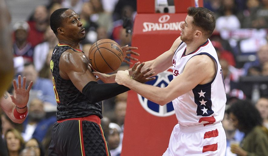 Washington Wizards forward Jason Smith, right, and Atlanta Hawks center Dwight Howard, left, reach for the ball during the first half in Game 2 of a first-round NBA basketball playoff series, Wednesday, April 19, 2017, in Washington. (AP Photo/Nick Wass)