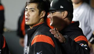 Miami Marlins starting pitcher Wei-Yin Chen, left, is pulled after the seventh inning of a baseball game against the Seattle Mariners by manager Don Mattingly, right, Tuesday, April 18, 2017, in Seattle. (AP Photo/Ted S. Warren)