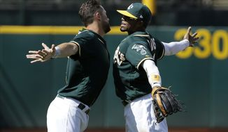 Oakland Athletics' Trevor Plouffe, left, and Rajai Davis celebrate after the team's baseball game against the Texas Rangers in Oakland, Calif., Wednesday, April 19, 2017. The Athletics won 9-1. (AP Photo/Jeff Chiu)
