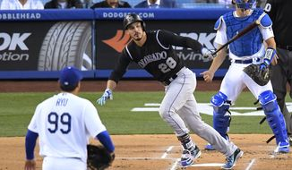 Colorado Rockies' Nolan Arenado, center, watches his two-run home run off Los Angeles Dodgers starting pitcher Hyun-Jin Ryu, left, during the first inning of a baseball game, Tuesday, April 18, 2017, in Los Angeles. (AP Photo/Mark J. Terrill)