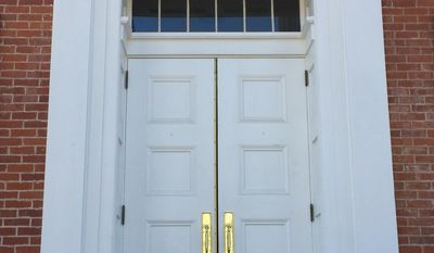 This March 12, 2017 photo shows the doors of the Lyceum, a building on the University of Mississippi campus in Oxford, Miss. A hole over the door on the left is the result of a bullet that hit the building when riots erupted on campus in 1962 over the enrollment of the university's first African-American student. The hole, which hollowed out over time, has been preserved by the university as a reminder of the episode. (AP Photo/Beth J. Harpaz)