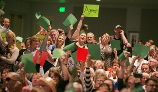 Attendees hold up green paper in solidarity with a speaker who asked a question during a town hall at Meridian Middle School in Meridian, Idaho, Wednesday, April 19, 2017. Idaho's Republican U.S. Rep. Raul Labrador is holding a town hall, the first of the state's congressional delegation to do so since the November election. (Kyle Green/Idaho Statesman via AP)