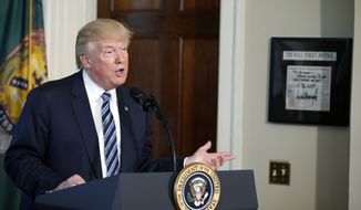 President Donald Trump speaks at the Treasury Department in Washington, Friday, April 21, 2017. On the wall next to Trump is a framed copy of a Wall Street Journal article signed by Trump to Treasury Secretary Steve Mnuchin. (AP Photo/Alex Brandon)