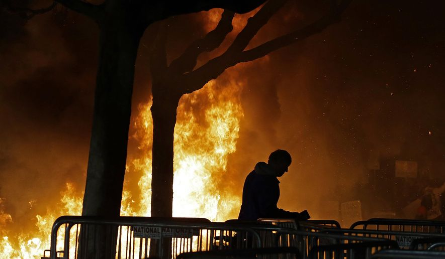 """In this Feb. 1, 2017 file photo, a fire set by demonstrators protesting a scheduled speaking appearance by Breitbart News editor Milo Yiannopoulos burns on Sproul Plaza on the University of California, Berkeley campus. The campus is bracing for a showdown next week, when the conservative provocateur Ann Coulter has vowed to speak in defiance of the university's wishes. Officials, police and the campus Republicans who invited Coulter, say there are valid concerns for violence in what is being called an ongoing """"Battle of Berkeley."""" (AP Photo/Ben Margot, File)"""