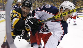 Pittsburgh Penguins' Carter Rowney (37) and Columbus Blue Jackets' Alexander Wennberg (10) battle for the puck in the corner during the second period in Game 5 of an NHL first-round hockey playoff series in Pittsburgh, Thursday, April 20, 2017. (AP Photo/Gene J. Puskar)