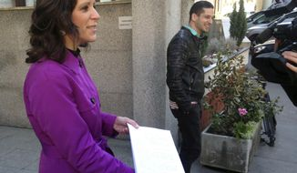 Bernadett Szel, a lawmaker from the green party Politics Can Be Different, shows a copy of an appeal she presented to the Constitutional Court outside the court's headquarters on Friday, April 21, 2017. Szel and other opposition lawmakers are seeking the repeal of amendments to the law on higher education they say seeks to shut down Budapest-based Central European University, founded by billionaire philanthropist George Soros. (AP Photo/Pablo Gorondi)