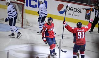 Washington Capitals right wing Justin Williams (14) celebrates his winning goal with Marcus Johansson (90), of Sweden, in the overtime of Game 5 in an NHL Stanley Cup hockey first-round playoff series as Toronto Maple Leafs center Auston Matthews (34) and defenseman Matt Hunwick (2) skate away, Friday, April 21, 2017, in Washington. (AP Photo/Nick Wass)