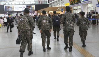 In this Thursday, April 20, 2017 photo, South Korean army soldiers walk to take their trains at Seoul Railway Station in Seoul, South Korea. A watchdog group says South Korea's army is hunting down and prosecuting gay servicemen after a video of two male soldiers having sex was posted on the internet earlier this year, stoking fear in an already persecuted minority group. (AP Photo/Ahn Young-joon)