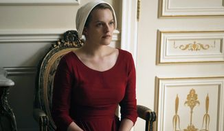 "This image released by Hulu shows Elisabeth Moss as Offred in a scene from, ""The Handmaid's Tale,"" premiering Wednesday on Hulu with three episodes. The remaining seven hours will be released each Wednesday thereafter. (George Kraychyk/Hulu via AP)"