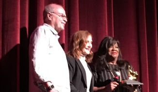 """Isabelle Huppert (center) was presented with a """"Golden Thumb"""" award by Chaz Ebert (right) at Ebertfest 2017 Friday.  (Eric Althoff/The Washington Times)"""