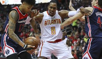 Atlanta Hawks' Dwight Howard battles Washington Wizards' Kelly Oubre Jr. and Bojan Bogdanovic, right, under the basket during Game 3 of a first-round NBA basketball playoff series Saturday, April 22, 2017, in Atlanta. (Curtis Compton/Atlanta Journal-Constitution via AP)