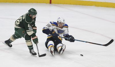 St. Louis Blues' Scottie Upshall (10) and Minnesota Wild's Jared Spurgeon (46) go after the puck during the second period of Game 5 of an NHL hockey Stanley Cup first-round playoff series Saturday, April 22, 2017, in St. Paul, Minn. (AP Photo/Stacy Bengs)