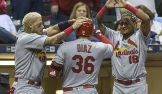 St. Louis Cardinals' Aledmys Diaz is greeted at the dugout by teammates Yadier Molina, left, and Yadier Molina after hitting a solo home run off of Milwaukee Brewers' Carlos Torres during the seventh inning of a baseball game Saturday, April 22, 2017, in Milwaukee. (AP Photo/Tom Lynn)
