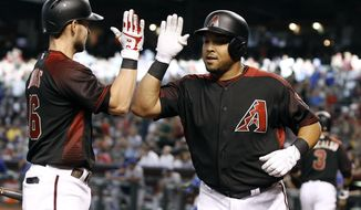 Arizona Diamondbacks' Yasmany Tomas, right, is congratulated by teammate Chris Owings after his solo home run against the Los Angeles Dodgers during the first inning of a baseball game, Saturday, April 22, 2017, in Phoenix. (AP Photo/Ralph Freso)