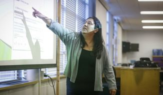ADVANCE FOR USE SATURDAY, APRIL 22 - In this April 11, 2017 photo, Isabel Conn speaks with immigrant families during a program on, at North High School in Des Moines, Iowa. (Bryon Houlgrave/The Des Moines Register via AP)