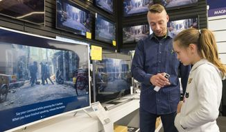 In this photo taken Saturday, April 15, 2017, Salome Sigurjonsdottir, 10, tests a voice-controlled television in an electronics store in Reykjavik. Sales assistant Einar Dadi said none of his TVs understood Icelandic. The revered Icelandic language, seen by many as a source of identity and pride, is being undermined by the widespread use of English both for mass tourism and in the voice-controlled artificial intelligence devices coming into vogue. (AP Photo/Egill Bjarnason)