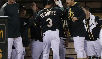 Oakland Athletics' Trevor Plouffe (3) celebrates in the dugout after his solo home run against the Seattle Mariners during the fifth inning of a baseball game Friday, April 21, 2017, in Oakland, Calif. (AP Photo/Marcio Jose Sanchez)