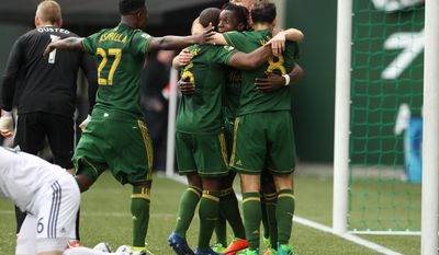 Teammates swarm Portland Timbers' Darren Mattocks following his first-half goal during an MLS soccer game against the Vancouver Whitecaps, Saturday, April 22, 2017, in Portland, Ore. (Pete Christopher/The Oregonian via AP)