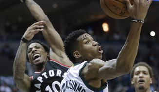 Milwaukee Bucks' Giannis Antetokounmpo rebounds in front of Toronto Raptors' DeMar DeRozan during the first half of Game 4 of an NBA first-round playoff series basketball game Saturday, April 22, 2017, in Milwaukee. (AP Photo/Morry Gash)
