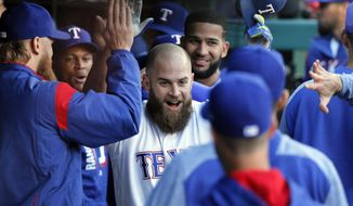Texas Rangers' Mike Napoli, center, celebrates with teammates in the dugout after hitting a solo home run during the second inning of the team's baseball game against the Kansas City Royals in Arlington, Texas, Saturday, April 22, 2017. (AP Photo/Tony Gutierrez)