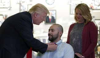 President Donald Trump, left, awards a Purple Heart to U.S. Army Sgt. First Class Alvaro Barrientos, with his wife Tammy Barrientos, right, at Walter Reed National Military Medical Center, Saturday, April 22, 2017, in Bethesda, Md. (AP Photo/Alex Brandon)