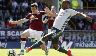 Burnley's Joey Barton, left, and Manchester United's Anthony Martial in action during their English Premier League soccer match at Turf Moor in Burnley, England, Sunday April 23, 2017. (Martin Rickett/PA via AP)