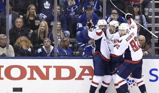 Washington Capitals center Marcus Johansson (90) celebrates with right wing Justin Williams (14) and center Evgeny Kuznetsov (92) after scoring against the Toronto Maple Leafs during Game 6 of an NHL hockey Stanley Cup first-round playoff series in Toronto on Sunday, April 23, 2017. The Washington Capitals beat the Maple Leafs 2-1 on Sunday to capture the best-of-seven Eastern Conference quarter-final series in six games. (Nathan Denette/The Canadian Press via AP)