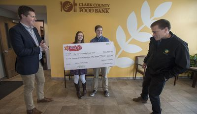 In this Friday, April 14, 2017 photo, Clark County Food Bank communications manager Matt Edmonds, left, looks over an oversized check as it is presented by Erin Ryan, 13, second from left, and her brother, Aidan Ryan, 17, with executive director Alan Hamilton, right, at the Clark County Food Bank in Vancouver, Wash. (Amanda Cowan/The Columbian via AP)