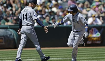 Seattle Mariners' Taylor Motter, right, is congratulated by third base coach Manny Acta (14) after hitting a grand slam off Oakland Athletics' Andrew Triggs in the third inning of a baseball game, Sunday, April 23, 2017, in Oakland, Calif. (AP Photo/Ben Margot)