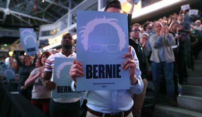 A local resident holds a sign as he listens to Sen. Bernie Sanders, I-Vt., speak at a rally for Omaha Democratic mayoral candidate Heath Mello, Thursday, April 20, 2017, in Omaha, Neb. (AP Photo/Charlie Neibergall)