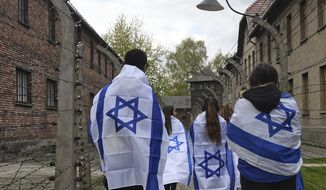 Participants of the yearly March of the Living walk between barbed wire fences in the former German Nazi Death Camp Auschwitz-Birkenau, in Oswiecim, Poland, Monday, April 24, 2017. Jews from Israel and around the world marched the 3km route from Auschwitz to Birkenau commemorating the Holocaust victims. (AP Photo/Alik Keplicz)